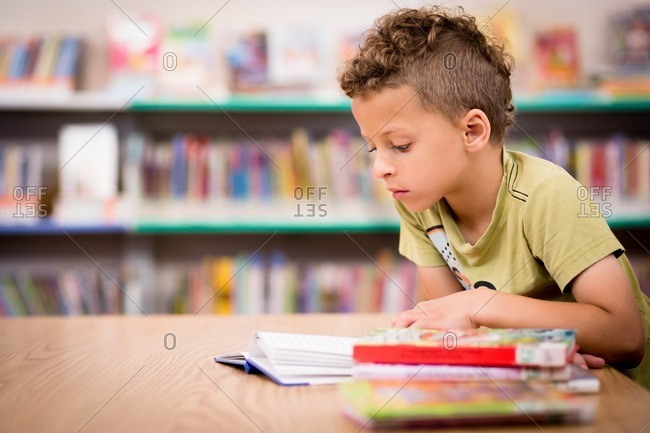 Little boy reading books in a library