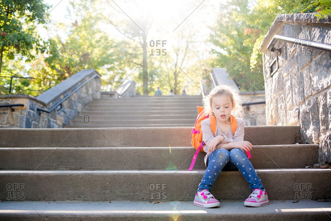 Girl with backpack on outdoor steps