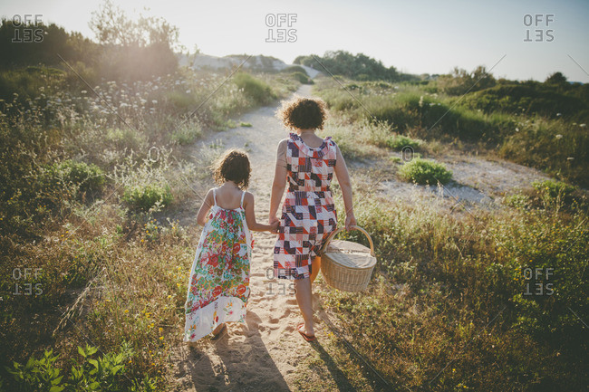 Mother and daughter holding hands walking to the beach with a picnic basket