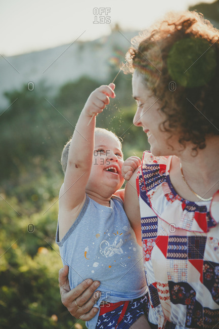 Toddler boy stroking his mother with a flower and laughing