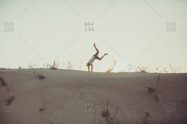 Man flipping on a sand dune and kicking up sand