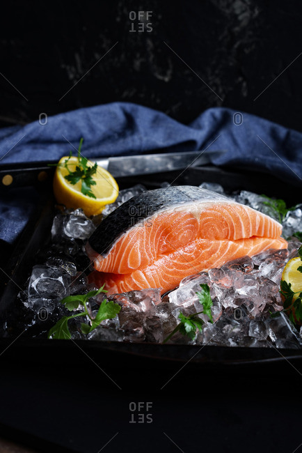 Two raw salmon fillets on ice