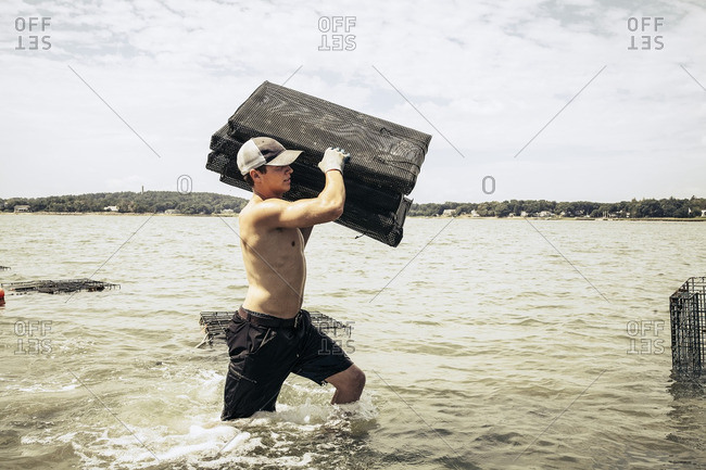 Man carrying oyster cages