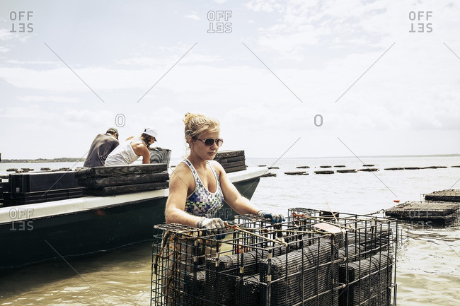 Woman carrying oyster cages