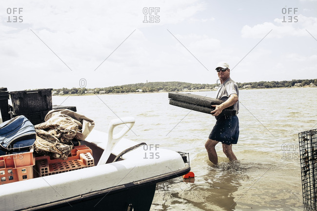 Man carrying oyster cages in sea