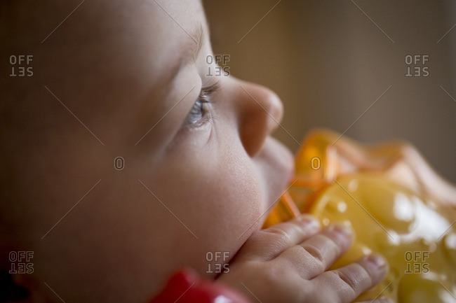A ten-month old child chews on a toy while seated in a bouncing chair