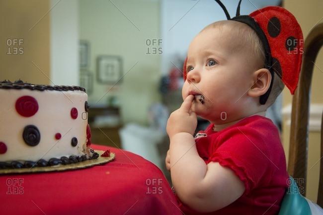 Baby eating cake wearing ladybug hat