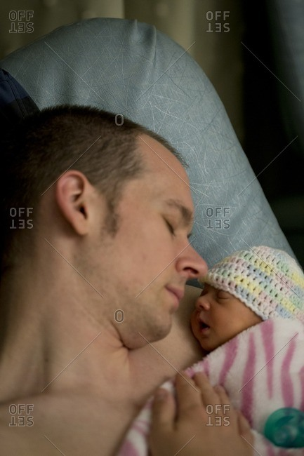 Father holding newborn to chest