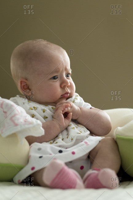 Young baby propped up by pillow