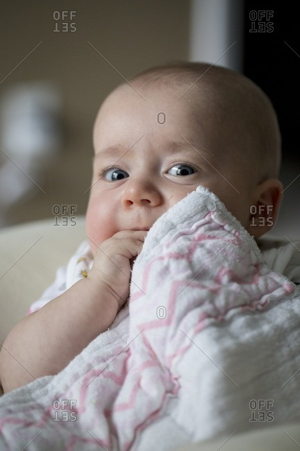 Baby making cute face with blanket