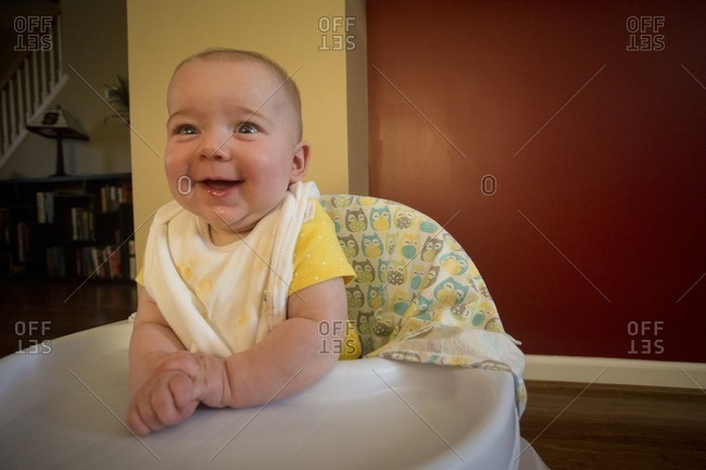 Baby in a walker toy smiling