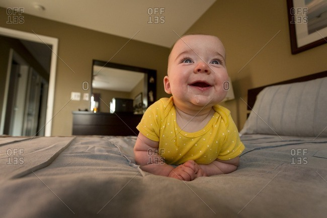 A happy baby smiles on adult bed