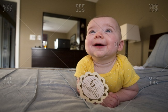Smiling baby with six months sticker