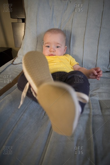 Baby girl in shoes on bed