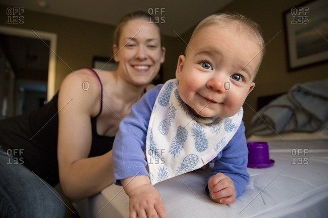 Mom holding smiling baby on bed