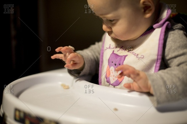 Baby playing with cereal in a high chair