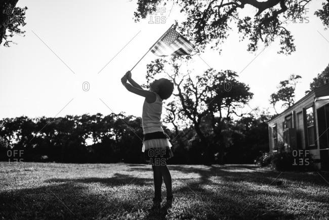 Girl waving American flag in yard