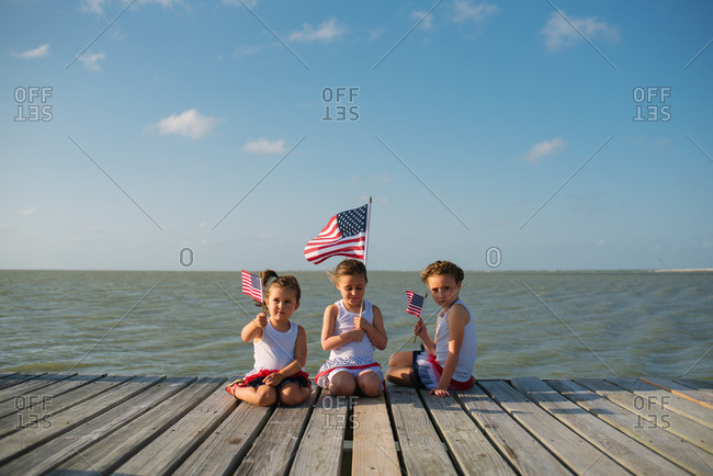 Girls with American flags on dock