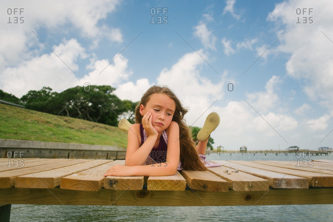 Girl staring off on a dock