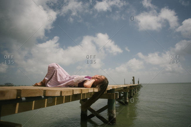 Girl with hair hanging off dock