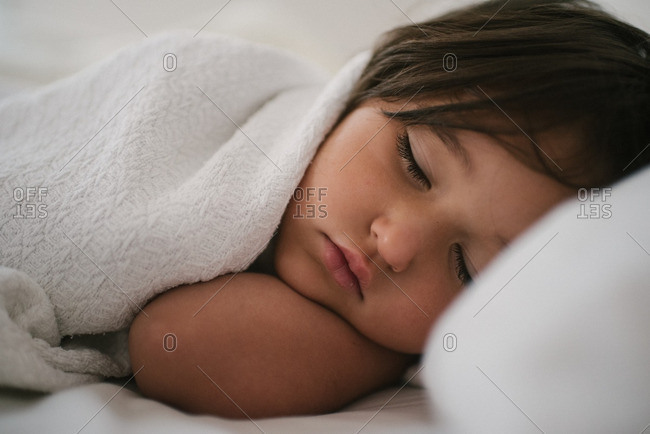 Portrait of little girl nested in bed