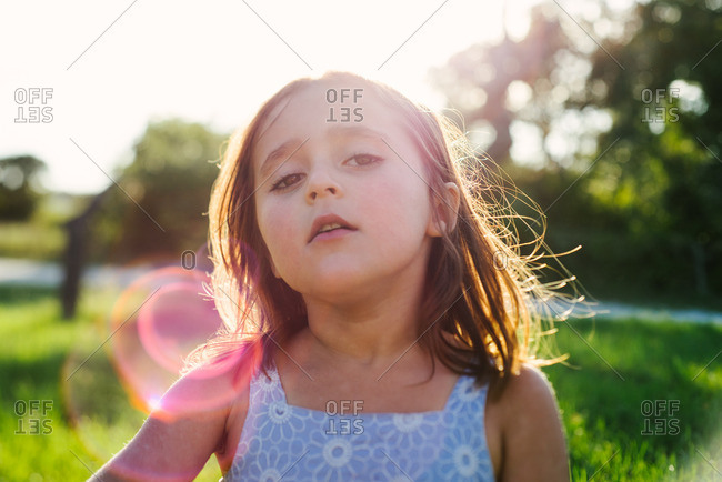 Girl in sun flare in field