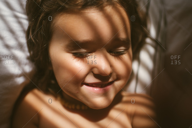 Smiling girl with closed eyes on bed