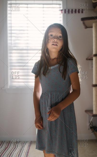 Girl in dress backlit by window