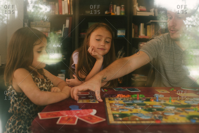 Dad and girls playing a board game