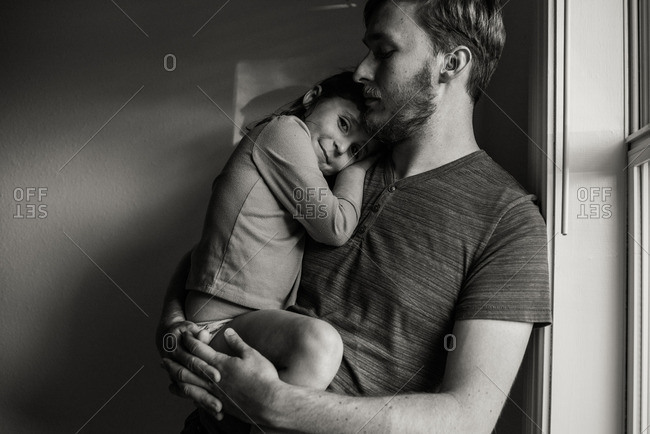 Dad holding girl by sunny window