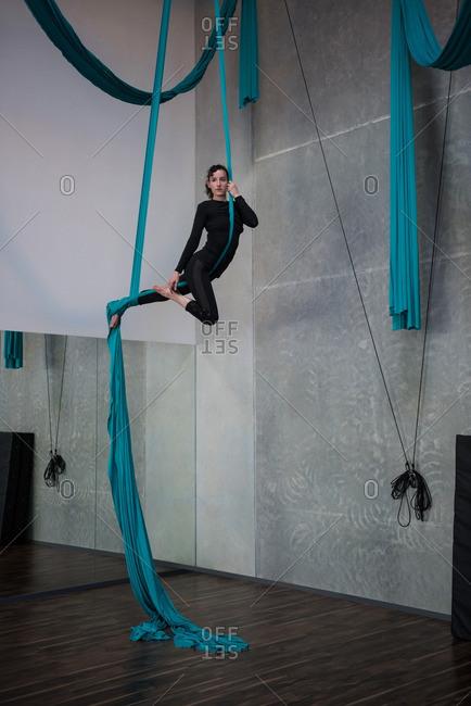 Gymnast exercising on blue fabric rope