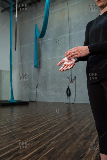 Gymnast rubbing chalk powder on her hands