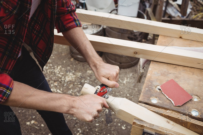 Man using a handheld tool to smooth and level the surface of a plank
