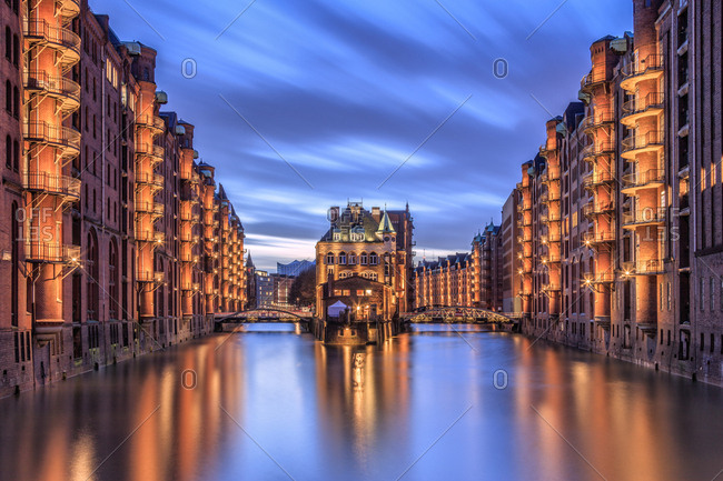 Blue dusk and lights are reflected in Poggenmohlenbrucke with water castle between bridges, Altstadt, Hamburg, Germany, Europe