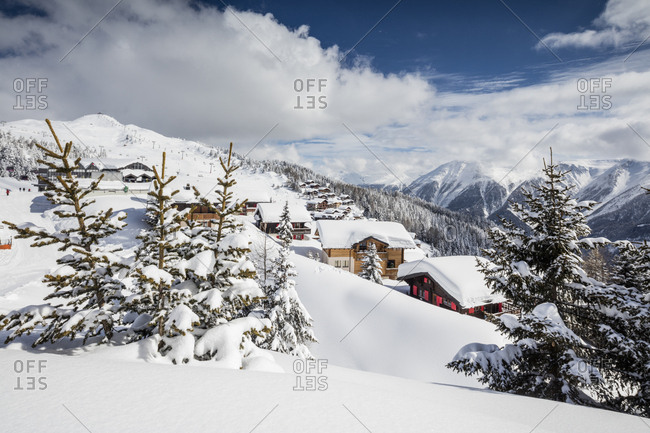 The winter sun shines on the snowy mountain huts and woods, Bettmeralp, district of Raron, canton of Valais, Switzerland, Europe