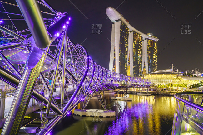 February 20, 2016: People strolling on the Helix Bridge towards the Marina Bay Sands and ArtScience Museum at night, Marina Bay, Singapore, Southeast Asia, Asia