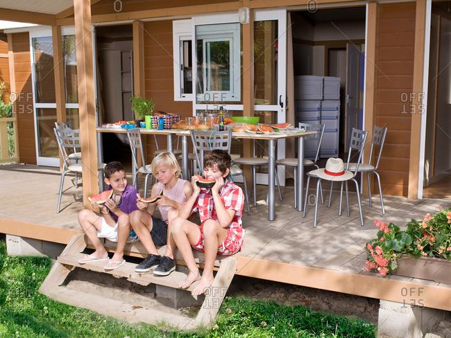 Boys eat watermelon sit on steps outside