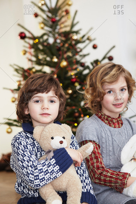 Kids with cuddly toys in front of tree