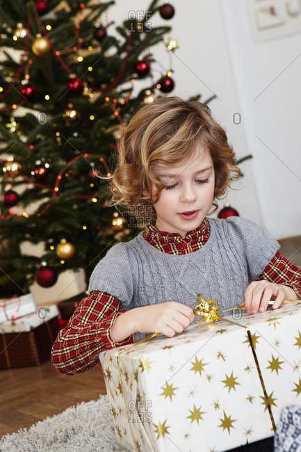 Girl with big present in front of tree