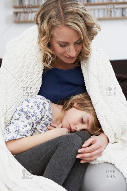 Girl sleeping in mothers lap