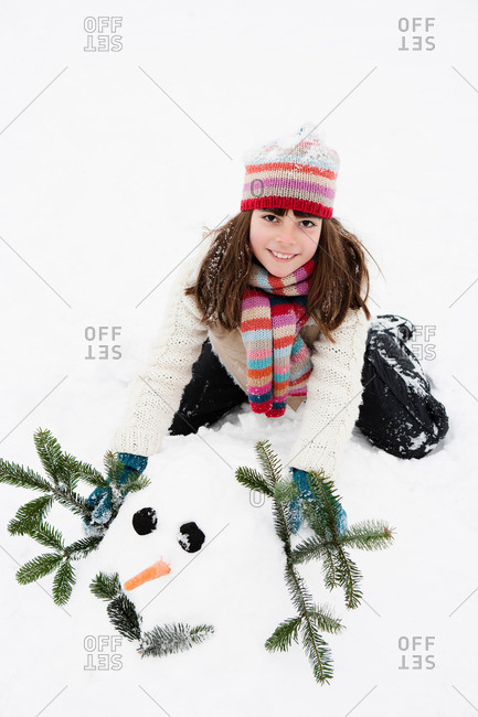 Girl decorating snowman