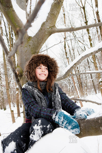Girl sitting under snowy tree