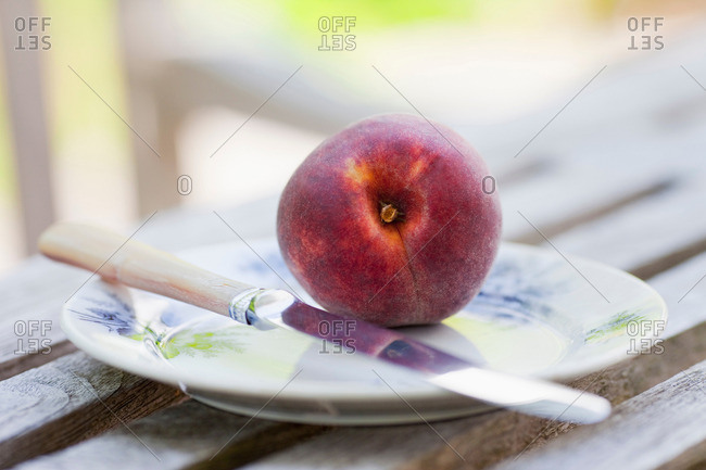 Peach on a plate with knife