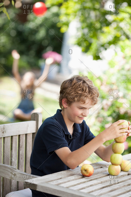 Boy building a tower out apples