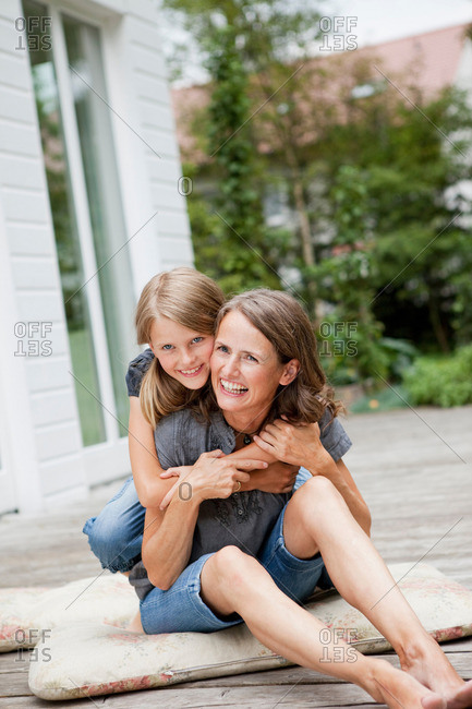 Mother and daughter hugging on patio