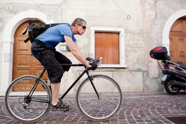 Man cycling through village
