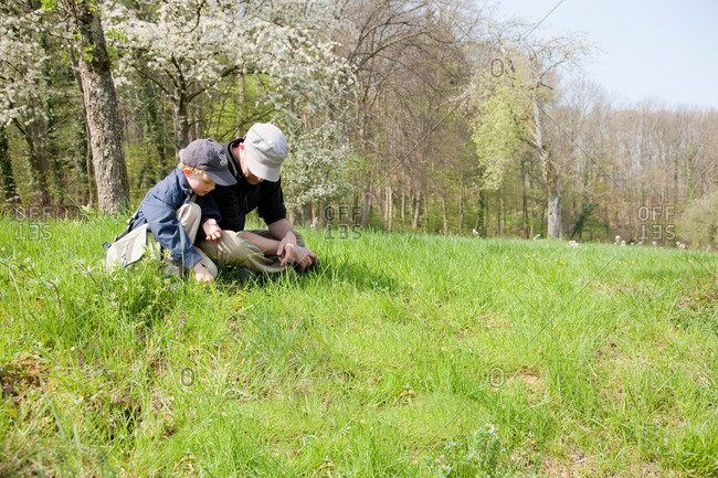 Father and son sitting in a field