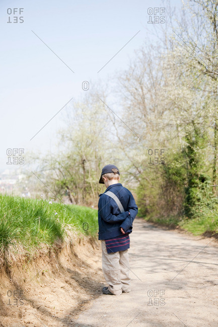 Boy in cap on dirt road