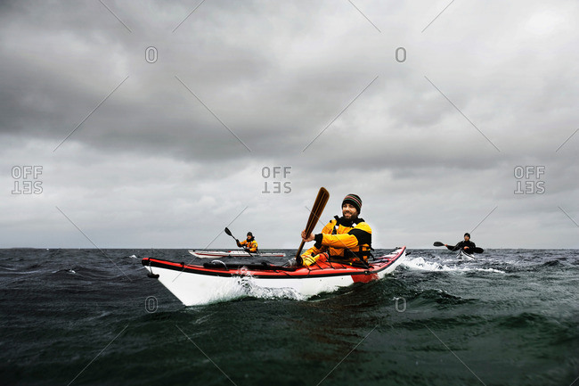 A group of three kayakers out on the sea