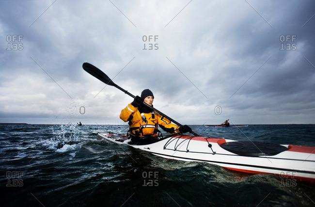 3 kayakers at see